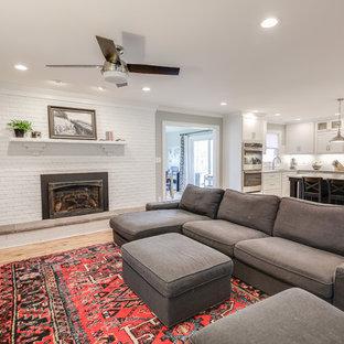他の地域の中サイズのコンテンポラリースタイルのおしゃれなファミリールーム (グレーの壁、淡色無垢フローリング、標準型暖炉、レンガの暖炉まわり、壁掛け型テレビ、茶色い床) の写真