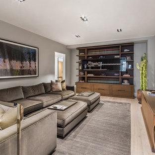 ニューヨークの中サイズのコンテンポラリースタイルのおしゃれな独立型ファミリールーム (淡色無垢フローリング、暖炉なし、壁掛け型テレビ、グレーの壁、ベージュの床) の写真