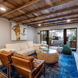 ニューヨークのコンテンポラリースタイルのおしゃれなファミリールーム (淡色無垢フローリング、白い壁、標準型暖炉、レンガの暖炉まわり、壁掛け型テレビ、ベージュの床) の写真