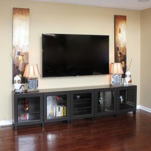 Esempio di un soggiorno moderno di medie dimensioni e aperto con pareti beige, pavimento in legno massello medio, camino classico e TV a parete