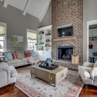 Inspiration for a mid-sized traditional open concept family room in Nashville with grey walls, medium hardwood floors, a standard fireplace, a brick fireplace surround and a wall-mounted tv.