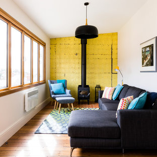 Eclectic open concept family room in Hobart with yellow walls, brown floor, medium hardwood floors and a wood stove.