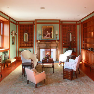 Example of a large classic open concept medium tone wood floor family room design in Philadelphia with green walls, a standard fireplace, a wood fireplace surround and no tv