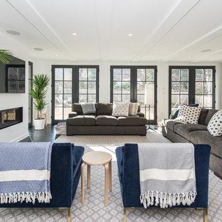 ワシントンD.C.の中サイズのトランジショナルスタイルのおしゃれなファミリールーム (白い壁、濃色無垢フローリング、壁掛け型テレビ、茶色い床、横長型暖炉) の写真