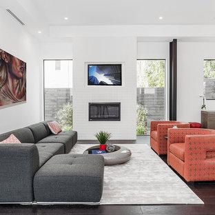 ロサンゼルスの広いコンテンポラリースタイルのおしゃれなオープンリビング (白い壁、濃色無垢フローリング、標準型暖炉、レンガの暖炉まわり、内蔵型テレビ) の写真