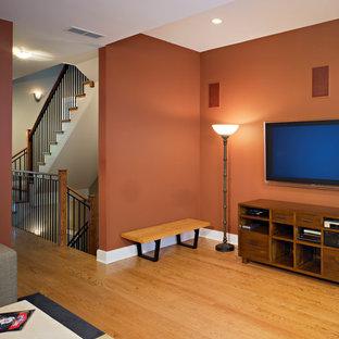 シカゴの中サイズのコンテンポラリースタイルのおしゃれなファミリールーム (オレンジの壁、無垢フローリング、壁掛け型テレビ) の写真