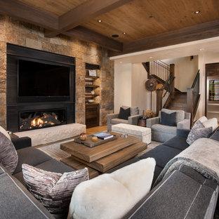 Imagen de sala de estar con barra de bar abierta, rústica, extra grande, con paredes beige, suelo de madera clara, marco de chimenea de metal, televisor colgado en la pared y chimenea lineal