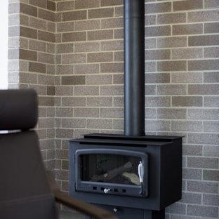 キャンベラの中サイズのコンテンポラリースタイルのおしゃれなファミリールーム (薪ストーブ、レンガの暖炉まわり) の写真