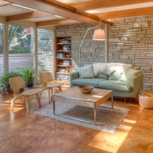 На фото: гостиная комната в стиле ретро с бежевыми стенами, бетонным полом и оранжевым полом