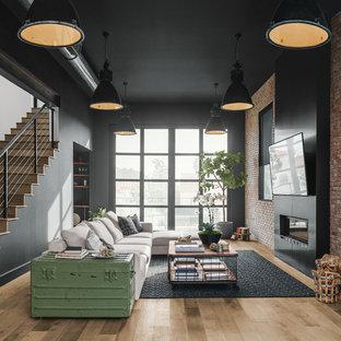 広いインダストリアルスタイルのおしゃれなオープンリビング (黒い壁、横長型暖炉、金属の暖炉まわり、壁掛け型テレビ、無垢フローリング、茶色い床) の写真