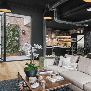 Imagen de sala de estar abierta, urbana, grande, con paredes negras, suelo laminado y suelo marrón