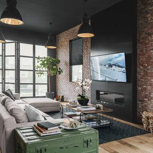 Industriell inredning av ett stort allrum med öppen planlösning, med svarta väggar, en väggmonterad TV, en bred öppen spis, en spiselkrans i metall och laminatgolv