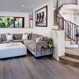 Inspiration for a large mediterranean medium tone wood floor family room remodel in San Diego with white walls, a standard fireplace, a stone fireplace and a wall-mounted tv