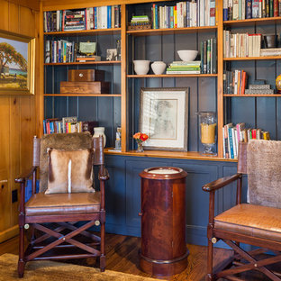 Imagen de sala de estar con biblioteca cerrada, rústica, pequeña, sin chimenea, con paredes azules, suelo de madera en tonos medios, pared multimedia y suelo marrón