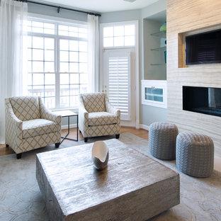 ワシントンD.C.の中サイズのコンテンポラリースタイルのおしゃれなファミリールーム (青い壁、無垢フローリング、両方向型暖炉、金属の暖炉まわり、壁掛け型テレビ、茶色い床) の写真