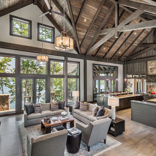 This is an example of a rustic open plan family and games room in Other with white walls, a standard fireplace, a stone fireplace surround, a wall mounted tv and light hardwood flooring.