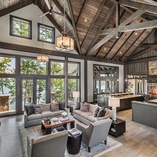 Foto de sala de estar abierta, rústica, con paredes blancas, chimenea tradicional, marco de chimenea de piedra, televisor colgado en la pared y suelo de madera clara