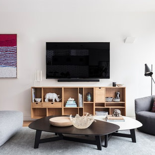 Contemporary open concept family room in Sydney with white walls, light hardwood floors and a wall-mounted tv.
