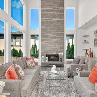 Cette photo montre une grand salle de séjour tendance ouverte avec un mur blanc, un sol en bois brun, cheminée suspendue, un manteau de cheminée en pierre, un téléviseur fixé au mur et un sol gris.