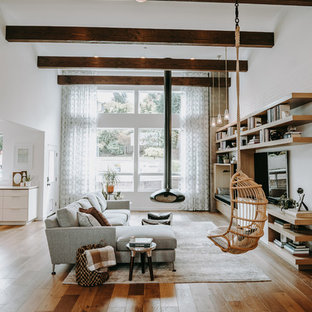 Inspiration for a contemporary medium tone wood floor and brown floor family room remodel in Seattle with white walls, a hanging fireplace and a wall-mounted tv
