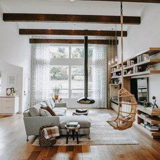 Immagine di un soggiorno contemporaneo con pareti bianche, pavimento in legno massello medio, camino sospeso, TV a parete e pavimento marrone