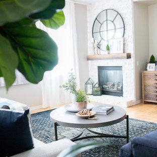 Exemple d'une salle de séjour romantique de taille moyenne et ouverte avec un mur gris, un sol en bois clair, une cheminée standard, un manteau de cheminée en pierre, un téléviseur fixé au mur et un sol jaune.