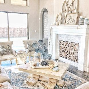 ダラスの大きいビーチスタイルのおしゃれなファミリールーム (グレーの壁、濃色無垢フローリング、標準型暖炉、壁掛け型テレビ、茶色い床、木材の暖炉まわり) の写真