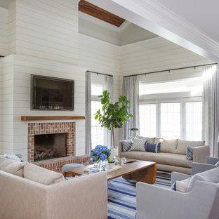 ジャクソンビルのビーチスタイルのおしゃれなファミリールーム (白い壁、無垢フローリング、標準型暖炉、レンガの暖炉まわり、壁掛け型テレビ、茶色い床) の写真