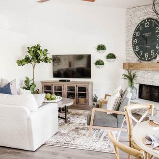 フェニックスの中サイズのビーチスタイルのおしゃれなファミリールーム (白い壁、ラミネートの床、コーナー設置型暖炉、石材の暖炉まわり、壁掛け型テレビ、グレーの床) の写真