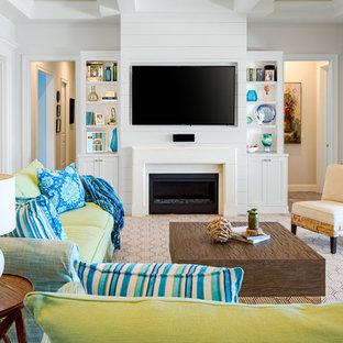 タンパの中サイズのビーチスタイルのおしゃれなファミリールーム (淡色無垢フローリング、標準型暖炉、石材の暖炉まわり、白い壁、壁掛け型テレビ、ベージュの床) の写真