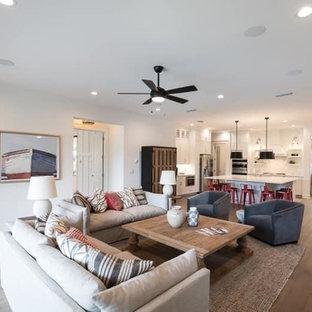 Modelo de sala de estar abierta, campestre, de tamaño medio, con paredes blancas, suelo de madera en tonos medios, chimenea de doble cara, marco de chimenea de ladrillo, televisor colgado en la pared y suelo marrón