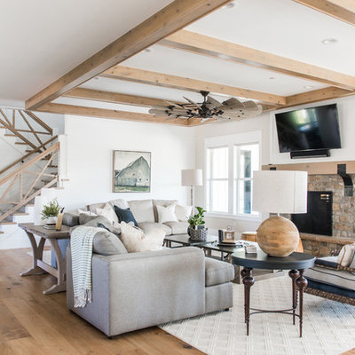 Example of a beach style open concept light wood floor family room design in Salt Lake City with white walls, a standard fireplace, a stone fireplace and a wall-mounted tv
