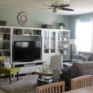 Aménagement d'une salle de séjour bord de mer de taille moyenne et ouverte avec un mur vert, aucune cheminée, un téléviseur indépendant et un sol en bois clair.