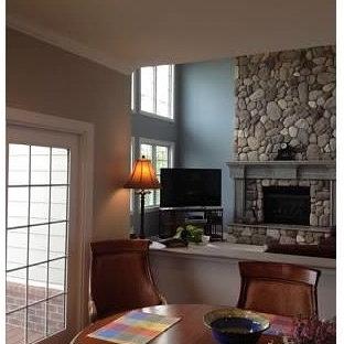 デトロイトの大きいビーチスタイルのおしゃれなファミリールーム (青い壁、カーペット敷き、標準型暖炉、石材の暖炉まわり、据え置き型テレビ) の写真
