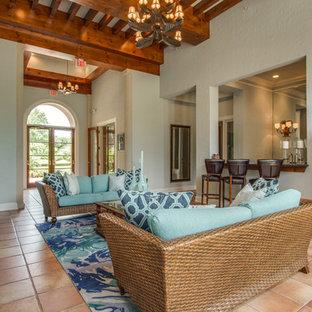 ヒューストンの中サイズのトロピカルスタイルのおしゃれな独立型ファミリールーム (青い壁、テラコッタタイルの床、標準型暖炉、オレンジの床) の写真