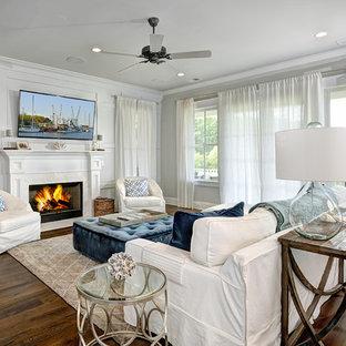 チャールストンのビーチスタイルのおしゃれなファミリールーム (グレーの壁、濃色無垢フローリング、標準型暖炉、壁掛け型テレビ) の写真