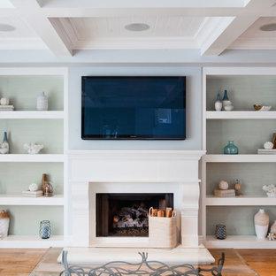 オレンジカウンティの大きいビーチスタイルのおしゃれなファミリールーム (青い壁、淡色無垢フローリング、標準型暖炉、漆喰の暖炉まわり、壁掛け型テレビ) の写真