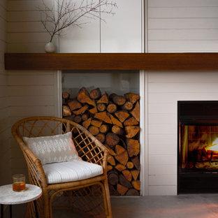 ポートランドの中くらいのビーチスタイルのおしゃれなオープンリビング (白い壁、淡色無垢フローリング、標準型暖炉、塗装板張りの暖炉まわり、テレビなし、ベージュの床、三角天井、塗装板張りの壁) の写真