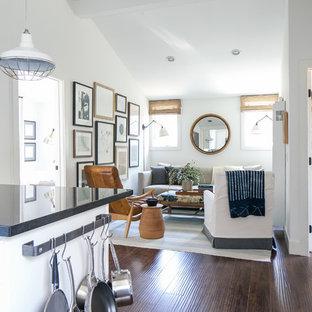 Modelo de sala de estar abierta, de estilo de casa de campo, pequeña, sin chimenea, con paredes blancas y suelo de madera oscura