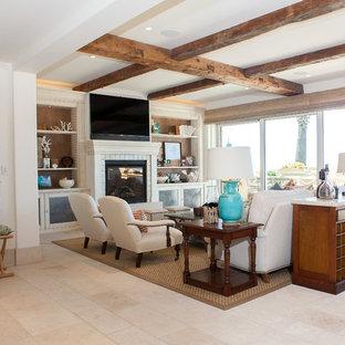 Imagen de sala de estar abierta, costera, grande, con paredes blancas, chimenea tradicional, marco de chimenea de baldosas y/o azulejos, televisor colgado en la pared y suelo de travertino