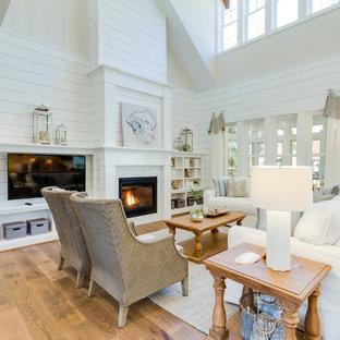 Ispirazione per un grande soggiorno aperto con pareti bianche, pavimento in legno massello medio, camino classico, cornice del camino in pietra, parete attrezzata e pavimento marrone