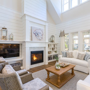 Beach style enclosed medium tone wood floor and brown floor family room photo in Other with white walls, a standard fireplace, a stone fireplace and a wall-mounted tv