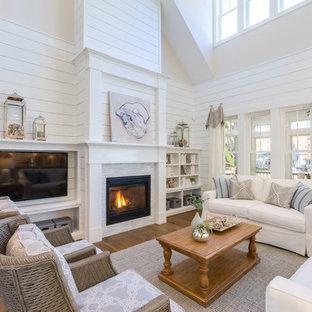 他の地域のビーチスタイルのおしゃれな独立型ファミリールーム (白い壁、無垢フローリング、標準型暖炉、石材の暖炉まわり、壁掛け型テレビ、茶色い床) の写真
