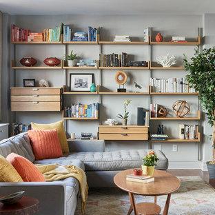Mittelgroßes, Abgetrenntes Klassisches Wohnzimmer ohne Kamin mit grauer Wandfarbe, braunem Holzboden, Wand-TV, braunem Boden und verputzter Kaminumrandung in New York