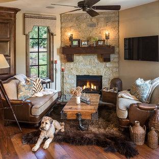 Idée de décoration pour une salle de séjour tradition avec un mur beige, un sol en bois brun, une cheminée d'angle, un manteau de cheminée en pierre, un téléviseur fixé au mur et un sol marron.