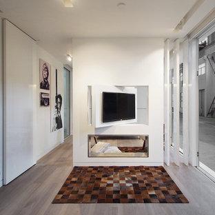 Modelo de sala de estar abierta, contemporánea, pequeña, con paredes blancas, suelo vinílico, chimenea de doble cara, marco de chimenea de metal y televisor colgado en la pared
