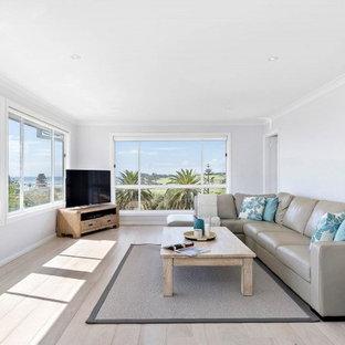 シドニーの広いビーチスタイルのおしゃれなオープンリビング (グレーの壁、淡色無垢フローリング、コーナー型テレビ、マルチカラーの床) の写真
