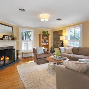 ボストンの中くらいのトラディショナルスタイルのおしゃれなオープンリビング (黄色い壁、無垢フローリング、コーナー設置型暖炉、タイルの暖炉まわり、壁掛け型テレビ、茶色い床) の写真
