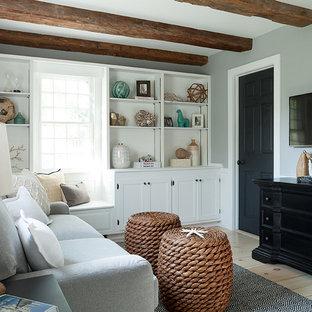 Ejemplo de sala de estar cerrada, marinera, pequeña, con paredes grises, suelo de madera clara y televisor colgado en la pared