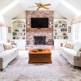 Foto de sala de estar cerrada, campestre, de tamaño medio, con paredes blancas, suelo de madera clara, chimenea tradicional, marco de chimenea de ladrillo, televisor colgado en la pared y suelo marrón